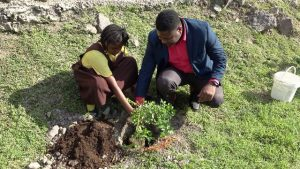 Hon. Troy Liburd, Junior Minister of Education, planting a fruit tree with a student of the St. Thomas' Primary School at the school grounds on January 29, 2020, to launch a tree planting programme by the Ministry and Department of Agriculture on Nevis