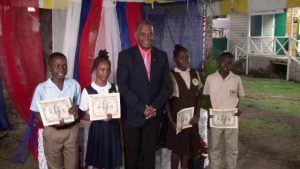 Hon. Eric Evelyn, Minister of Social Development (middle) with 2020 beneficiaries of the Alexander Hamilton Scholarship Fund (l-r) Mr. Jae-Ele Swanston; Ms. Kaya Williams-Mulraine; Ms. Noella Maynard; and Mr. Stephan Leader