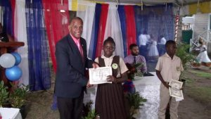 Hon Eric Evelyn, Minister of Social Development presenting Alexander Hamilton Scholarship certificate and $500 cheque to Ms. Noella Maynard form the Gingerland Secondary School, at the grounds of the Alexander Hamilton Museum in Charlestown recently. She is a 2020 beneficiary of the Alexander Hamilton Scholarship Fund