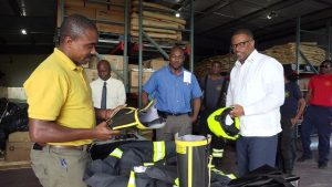 (Extreme left) Mr. Garfield Hodge, Officer in Charge of the St. Kitts and Nevis Fire and Rescue Services, Nevis Department; and Hon Mark Brantley, Premier of Nevis (extreme right) inspecting a number of protective fire suits at the Nevis Disaster Management Department's warehouse at Long Point on January 16, 2020, while (middle l-r) Mr. Wakely Daniel, Permanent Secretary in the Premier's Ministry; and Mr. Brian Dyer, Director of the Nevis Disaster Management Unit along with officers of the Nevis Fire and Rescue Services, Nevis Department look on