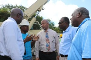 (second from left) Mr. Clychawn Wilson, Head of Water Production at the Nevis Water Department, speaking with (from his l-r) Hon. Spencer Brand, Minister of Water Services on Nevis; Mr. Denzil Stanley, Principal Assistant Secretary in the ministry; Mr. Floyd Robinson, Manager of the Water Resource Management Unit, and (left) Dr. Ernie Stapleton, Permanent Secretary in the Ministry of Water Services on site of the Hamilton well on January 16, 2020