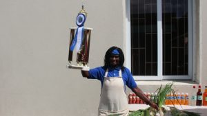 : Mrs. Emontine Thompson showing off her trophy and blue ribbon at her stall at the George Mowbray Hanley Market Complex in Charlestown, on February 24, 2020