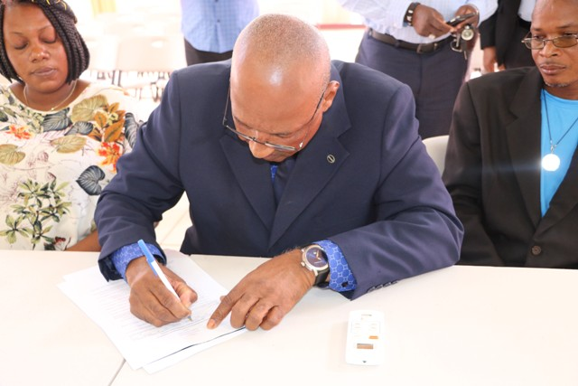"Mr. Keith ""Dis an Dat"" Scarborough, candidate for the Constituency Nevis 5, St. Thomas' Parish by-election signs the Statutory Declaration of a Person Nominated as a Candidate for Election as a Member of the Nevis Island Assembly on Nomination Day, February 25, 2020, at the Cotton Ground Community Centre, before Mrs. Sherilla Nisbett, Returning Officer for the Electoral District 5. He is flanked by his nominators (l) Ms. Shoya Matthew of Jessups Village and (r) Mr. Denzil Webbe of Cotton Ground"