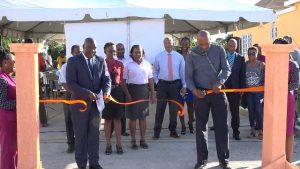 (l-r) Hon. Alexis Jeffers Minister of Lands and Housing in the Nevis Island Administration and Chairman of the Nevis Housing and Land Development Corporation and Mr. Keith Scarborough, Concerned Citizens Movement (CCM) Representative for the St. Thomas' Parish cut the ribbon to signal the official commissioning of the Colquhoun Manor Road constructed by the Nevis Housing and Land Development Corporation in Phase 2 at the Colquhoun Housing Development in Colquhoun Estate on February 13, 2020