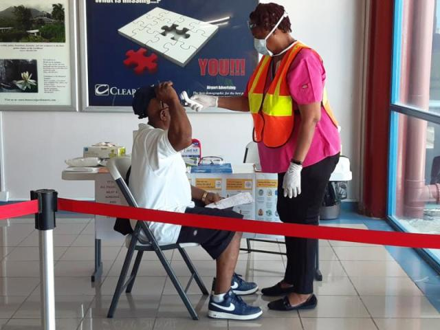 A nurse taking the temperature of a passenger on arrival at the Vance W. Amory International Airport as part of the Nevis Air and Sea Ports Authority's enhanced security measures in response to the COVID-19 pandemic