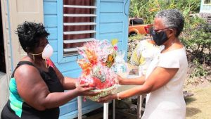 Her Honour Mrs. Hyleeta Liburd, Deputy Governor General on Nevis presenting a fruit basket to Mrs. Denise Browne for her mother-in-law, 103 year-old Mrs. Mary Brown of River Path, on behalf of His Excellency Sir Tapley Seaton, Governor General of St. Kitts and Nevis and the people of the Federation in observance of Centenarians Day celebrated on May 31, 2020
