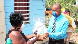 Hon Eric Evelyn presenting a gift basket to Mrs. Denise Browne for her 103 year-old mother-in-law Mrs. Mary Brown of River Path, on behalf of the Ministry of Social Services and the people of Gingerland in observance of Centenarians Day celebrated on May 31, 2020