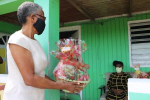Photo caption: Her Honour Mrs. Hyleeta Liburd, Deputy Governor General on Nevis presenting a fruit basket to 100 year-old Eliza Jeffers of Hamilton on behalf of His Excellency Sir Tapley Seaton, Governor General of St. Kitts and Nevis and the people of the Federation in observance of Centenarians Day celebrated on May 31, 2020