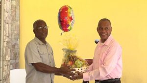 (L-r) Mr. Alsted Pemberton, outgoing Director of the Social Policy and Sustainable Human Development Unit, receives a fruit basket as a token of appreciation from Hon. Eric Evelyn, Minister of Social Development for his sterling contribution to the ministry and the people of Nevis at a retirement ceremony at the Nevis Performing Arts Centre courtyard on May 8, 2020