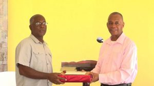 (L-r) Mr. Alsted Pemberton, outgoing Director of the Social Policy and Sustainable Human Development Unit, receives a gift as a token of appreciation from Hon. Eric Evelyn, Minister of Social Development for his sterling contribution to the ministry and the people of Nevis at a retirement ceremony at the Nevis Performing Arts Centre courtyard on May 8, 2020