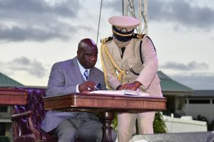 Hon. Alexis Jeffers, Deputy Premier of Nevis signs the official documents after taking his oath at the Inauguration Ceremony of the Team Unity Administration's Second Term at Warner Park in Basseterre on June 14, 2020