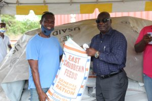 (L-r) Mr. Morris Hanley, one of 154 livestock farmers on Nevis receiving free animal feed in a Nevis Island Administration/Eastern Caribbean Group of Companies partnership from Hon. Alexis Jeffers, Deputy Premier of Nevis and Minister of Agriculture at Prospect on July 15, 2020