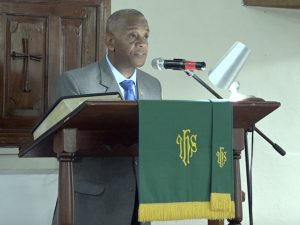 """Hon. Eric Evelyn, Senior Minister in the Nevis Island Administration, and Federal Minister of Environment and Cooperatives, reading a scripture at a """"United in Christ, Giving Thanks and Praise"""" church service at the Gingerland Methodist Church on July 19, 2020"""