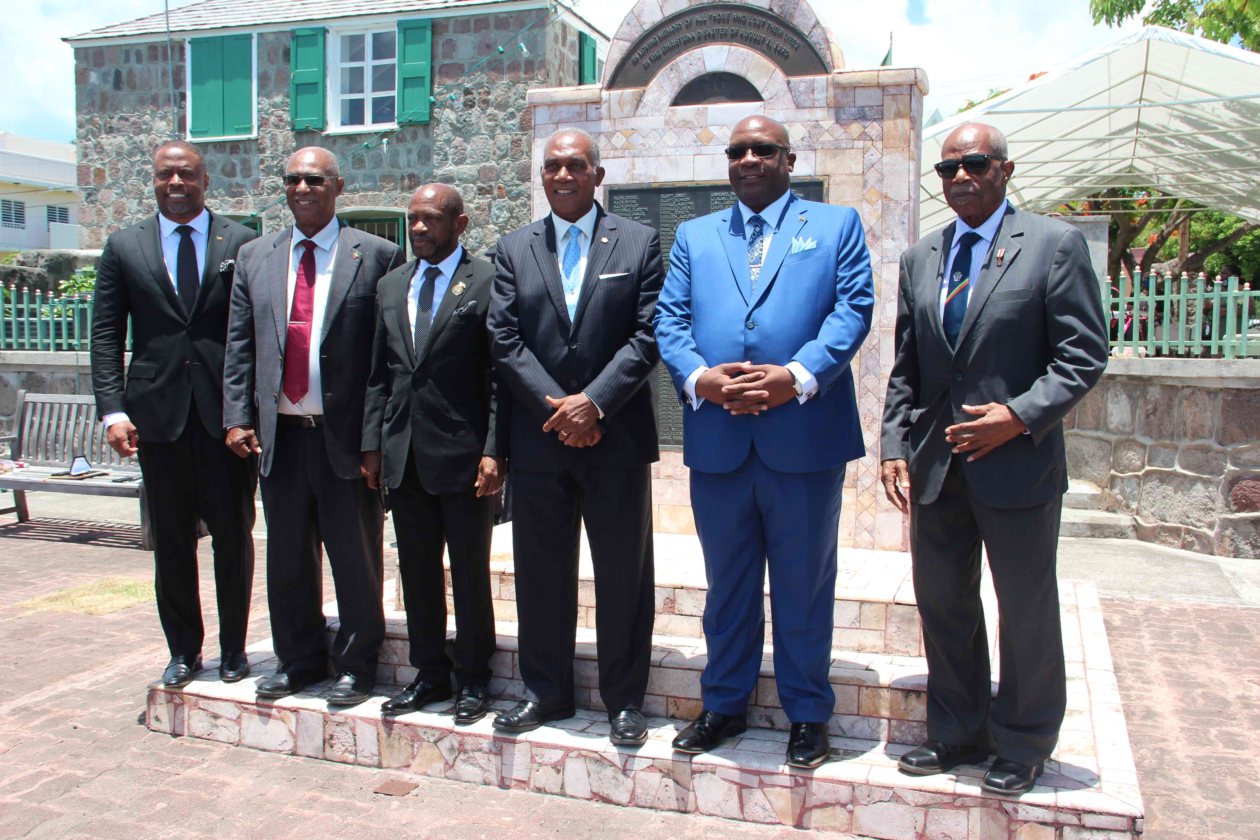Living prime ministers and premiers in St. Kitts and Nevis on July 31, 2020, standing before the monument erected outside the Nevis Island Assembly Chambers on Samuel Hunkins Drive in memory of those who perished in the MV Christena Disaster on August 01, 1970. (L-r) Hon. Mark. Brantley, Premier of Nevis; Hon. Joseph Parry, former Premier of Nevis; The Right Hon. Denzil Douglas, former Prime Minister of St. Kitts and Nevis; Hon. Vance Amory, former Premier of Nevis; Dr. the Hon. Timothy Harris, Prime Minister of St. Kitts and Nevis; and Dr. the Right Excellency and Right Hon. Sir Kennedy Simmonds, former Prime Minister of St. Kitts and Nevis
