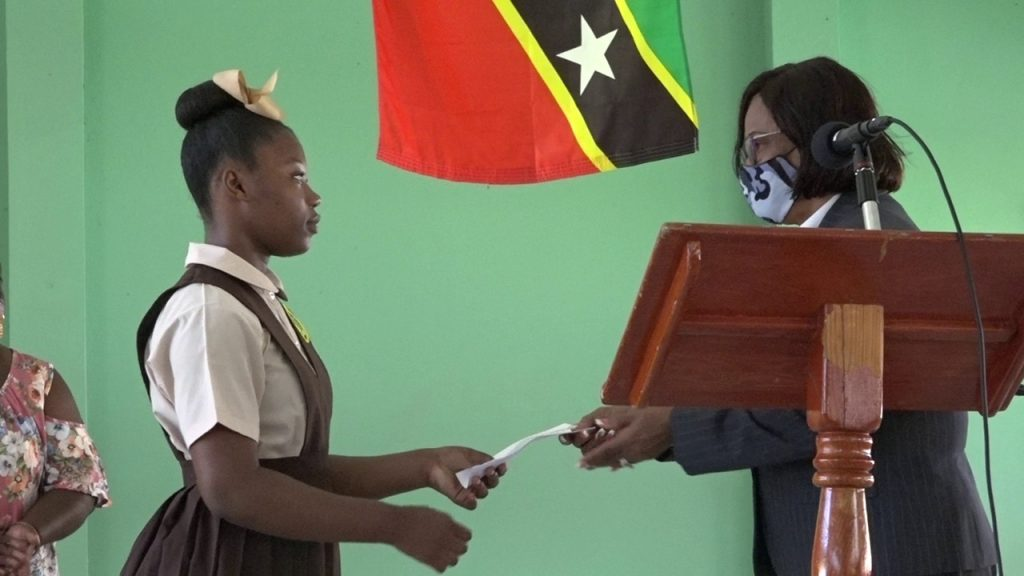 Ms. Nikelsia Kelly of the Gingerland Secondary School receives $1000 scholarship award from retired High Court Judge, the Honourable Pearletta Lanns at the school's auditorium on August 26, 2020