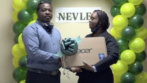 Mr. Kayno David, Deputy Principal at the Gingerland Secondary School, receiving a laptop from Ms. Antoinette Daniel, a member of the Nevis Electricity Company Limited's 20th Anniversary Organising Committee, at a handing over ceremony at the company's board room on August 26, 2020