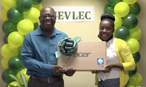 Mr. Juan Williams, Principal of the Charlestown Secondary School, receiving a laptop from Ms. Curleane Liburd, a member of the Nevis Electricity Company Limited's 20th Anniversary Organising Committee, at a handing over ceremony at the company's board room on August 26, 2020