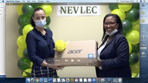 Ms. Joy Napier, Principal of the Nevis International High School, receiving a laptop from Ms. Hazel Chiverton, Chairperson of the Nevis Electricity Company Limited's 20th Anniversary Organising Committee, at a handing over ceremony at the company's board room on August 26, 2020