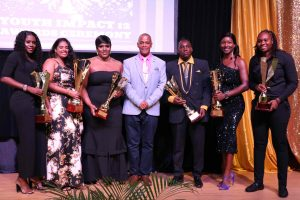 Hon. Eric Evelyn, Minister of Youth in the Nevis Island Administration (fourth from left) with the six awardees at the Youth Impact 12 Awards Ceremony hosted by the Department of Youth on August 12, 2020, at the Nevis Performing Arts Centre (l-r) Delcia Burke awarded for Volunteerism; Raveena Persaud awarded for Extraordinary Youth in Agriculture; Cecelia Stanley awarded for Youth in Entrepreneurship; Brandon Powell awarded for Youth in Technology; Verna Grant awarded for Education and Life-long Learning; and Melicia Clarke awarded for Sports Excellence