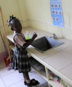 A Kindergarten student at the Charlestown Primary School learns proper hand washing technique