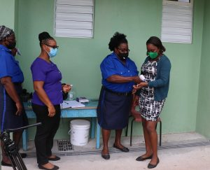 Staff at the entrance of the Charlestown Primary School checking the temperature of persons visiting the school