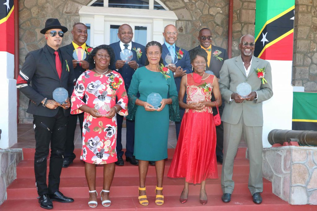 """Nine of the 10 awardees showing off their awards on the steps of the picturesque Government House at Belle Vue, moments after they received their Independence Day Awards from Her Honour Mrs. Hyleeta Liburd, Deputy Governor General on Nevis on September 19, 2020. Back row: (l-r) Mr. Austin Lescott; Captain James Greene; Mr. Vaughn Anslyn; and Mr. Oscar """"Astro"""" Browne. Front row: (l-r) Mr. Calver Lee """"Gharlic"""" Swanston; Ms. Laurel Smithen; Mrs. Althea E. Jones; Ms. Thelma E. Hunkins; and Mr. Winston Crooke"""