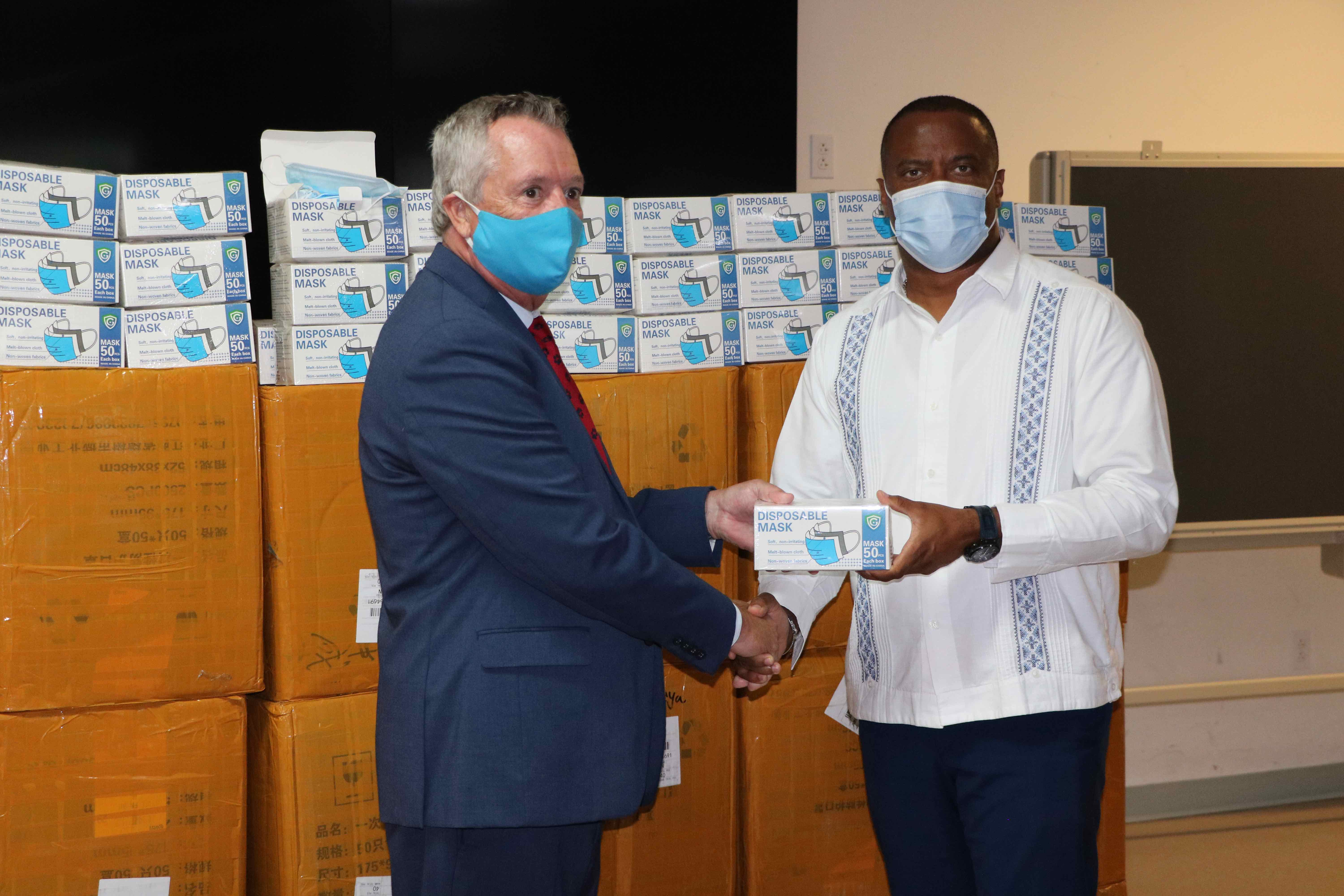 Premier of Nevis Hon. Mark Brantley, Senior Minister of Health in the Nevis Island Administration (r) accepting the donation of 100,000 disposable masks from Dr. Ralph Crum, Dean of the Medical University of the Americas at a handing over ceremony at the Emergency Operations Centre at Long Point on September 08, 2020