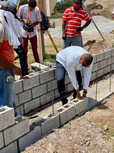 (l-r) Hon. Mark Brantley, Premier of Nevis lays a concrete block at the construction site during a tour of the St. Kitts and Nevis Pinney's Beach Park Project on September 15, 2020