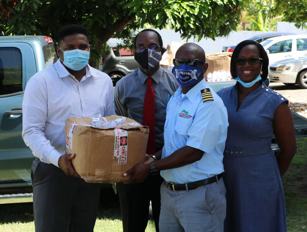 (l-r) Hon. Troy Liburd, Junior Minister of Education in the Nevis Island Administration; and Kevin Barrett, Permanent Secretary in the Ministry of Education, accepting a donation of 2000 bottles of hand sanitizer on September 14, 2020, from Mr. Wincent Perkins and his wife Mrs. Delvise Perkins, owners of local company Islander Watersports