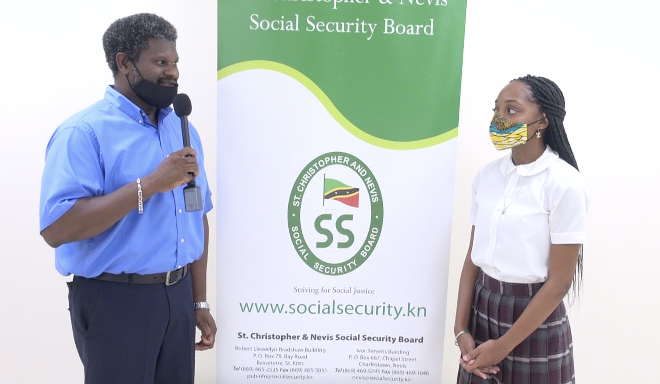 l-r) Mr. Donovan Herbert, Senior Branch Manager of the St. Christopher and Nevis Social Security Board, Nevis Branch thanking Ms. Zwena Jones of Zee's Exquisite Apparel Line (ZEAL), a budding entrepreneur, recipient of a St. Christopher and Nevis Social Security Board Scholarship and a student of the Nevis Sixth Form College at the Social Security's Board Room at Pinney's Estate on September 25, 2020, for her donation of 25 fabric masks to the Branch members to assist in their fight against COVID-19