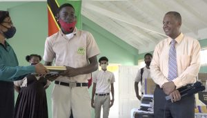 Fifth form student Lebron Senior accepting school supplies from Mrs. Lineth Williams, Principal of the Gingerland Secondary School n October 09, 2020, while Hon. Eric Evelyn Minister of Youth and Community Development in the Nevis Island Administration, and area representative for St. George's, Gingerland who donated the supplies looks on