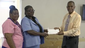 Hon. Eric Evelyn, Minister of Youth, Community Development, and Area Representative for St. George's Gingerland presenting a financial donation to Ms. Dawnny Lanns, Education Officer responsible for the Gingerland Preschool on behalf of the school on October 09, 2020. Ms. Pamela Elliott, Supervisor of the Gingerland Preschool looks on