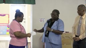 (l-r) Ms. Pamela Elliott, Supervisor of the Gingerland Preschool accepting a cheque from Ms. Dawnny Lanns, Education Officer responsible for the Gingerland Preschool donated by Hon. Eric Evelyn, Minister of Youth and Community Development in the Nevis Island Administration, and area representative for St. George's, Gingerland on October 09, 2020, while Mr. Evelyn looks on