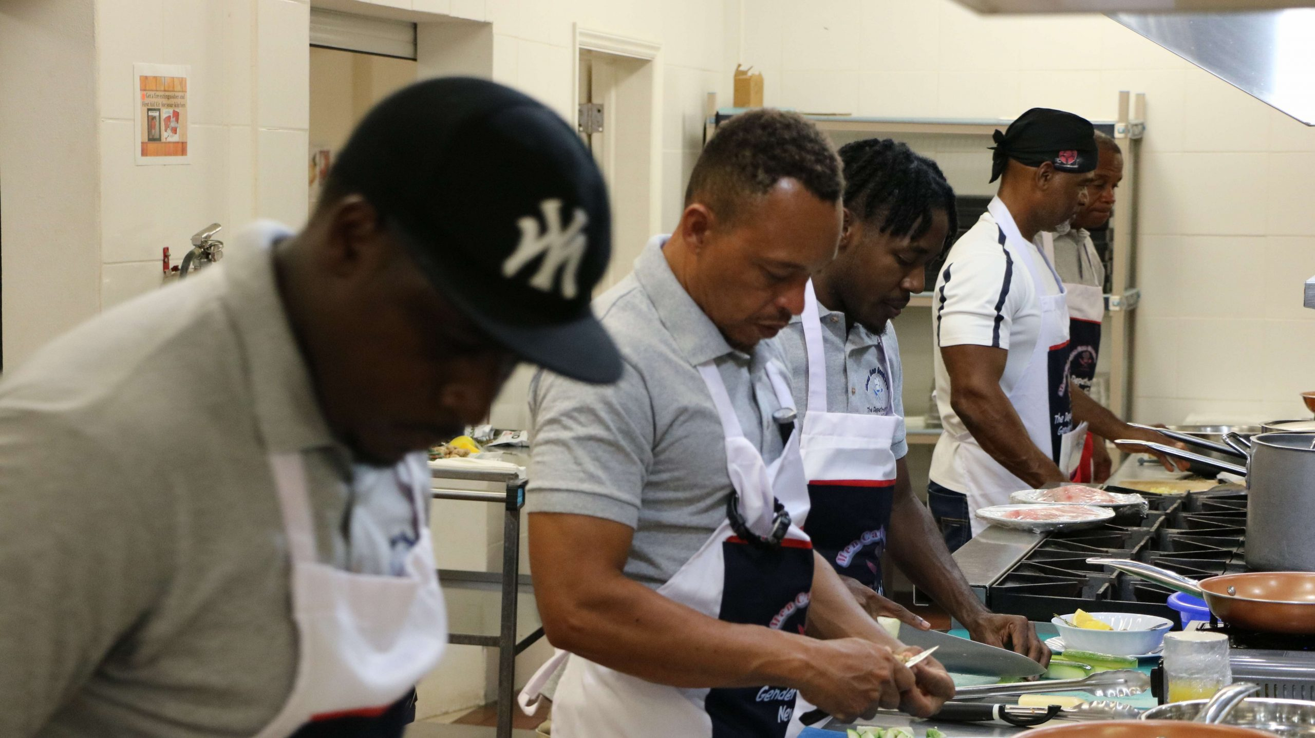 """Participants in the Department of Gender Affair's """"Men Can Cook"""" programme during a session at the Charlestown Primary School's Cafeteria on November 23, 2020"""