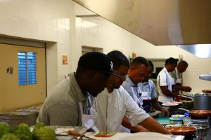 """Chef Michael Henville (second from left) instructing participants at the Department of Gender Affairs """"Men Can Cook"""" programme during a session at the Charlestown Primary School's Cafeteria on November 23, 2020"""