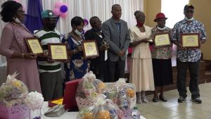 (l-r) Constantia David, Reuben Williams; Violet Perkins; Essie Delashley (caregiver); Hon. Eric Evelyn, Minister of Social Development in the Nevis Island Administration; Janet Herbert (caregiver); Bernadette Lewis; and Carlton Pinney during an October 29, 2020 Senior Citizens Awards Ceremony & Luncheon hosted by the Department of Social Services at the Jessups Community Centre