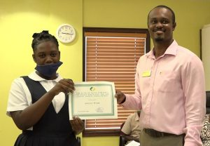 Adeille Webbe of the Charlestown Secondary School receiving the Bank of Nevis Limited's Right Excellent Dr. Sir Simeon Daniel Scholarships for 2020 presented by Mr.Pheon Jones, Marketing Officer and Member of the Scholarship Committee on December 04, 2020