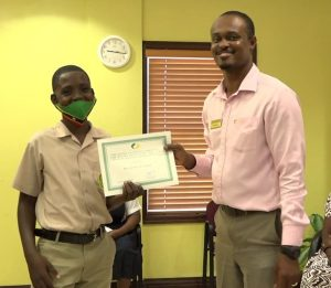 Mr. Benjamin Clarke of the Gingerland Secondary School receiving the Bank of Nevis Limited's Right Excellent Dr. Sir Simeon Daniel Scholarships for 2020 presented by Pheon Jones, Marketing Officer and Member of the Scholarship Committee on December 04, 2020