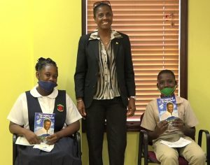 (standing) Mrs. Janice Daniel-Hodge, daughter of the late Sir Simeon presenting recipients of the Bank of Nevis Limited's Right Excellent Dr. Sir Simeon Daniel Scholarships for 2020 (seated left) Adeille Webbe of the Charlestown Secondary School and (seated right) Benjamin Clarke of the Gingerland Secondary School with copies of the biography of the late Sir Simeon during a ceremony on December 04, 2020