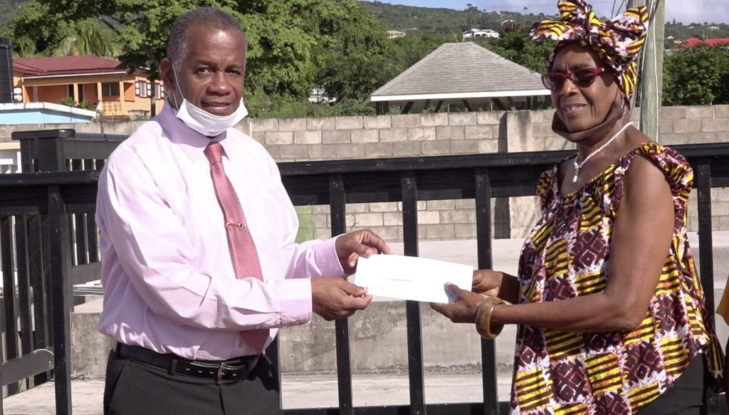 Hon. Eric Evelyn, Minister of Culture on Nevis accepting a monetary donation from Mrs. Gloria Anslyn, on behalf of the first Culturama Committee at the Cultural Complex in Charlestown on December 02, 2020