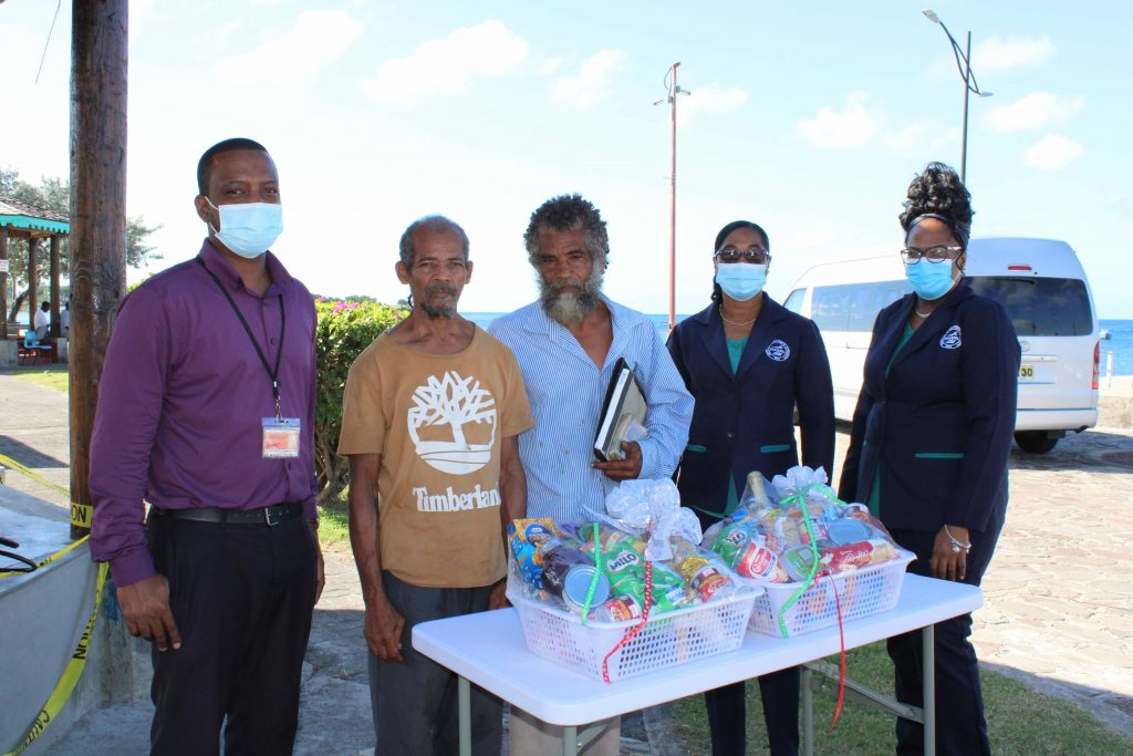 (L-R) Mr. Kenny Warner, Operations Supervisor at the Charlestown Sea Port; Mr. Raoul Archibald; and Mr. Donald Browne, two of the four sanitation workers from the Ministry of Health, honoured by the Nevis Air and Sea Ports Authority, Ms. Loretta France, Human Resource Manager; and Ms. Michelle Lawrence, Administrative Officer, at an appreciation ceremony at the Charlestown Sea Port on Monday 21, December 2020