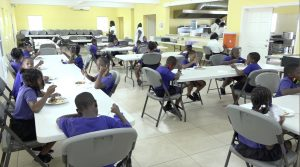 """Students of the Joycelyn Liburd Primary School in Gingerland enjoying the national dish of Belize as part of the """"Tour around the Caribbean"""" initiative introduced in the Department of Education's School Meals Programme"""