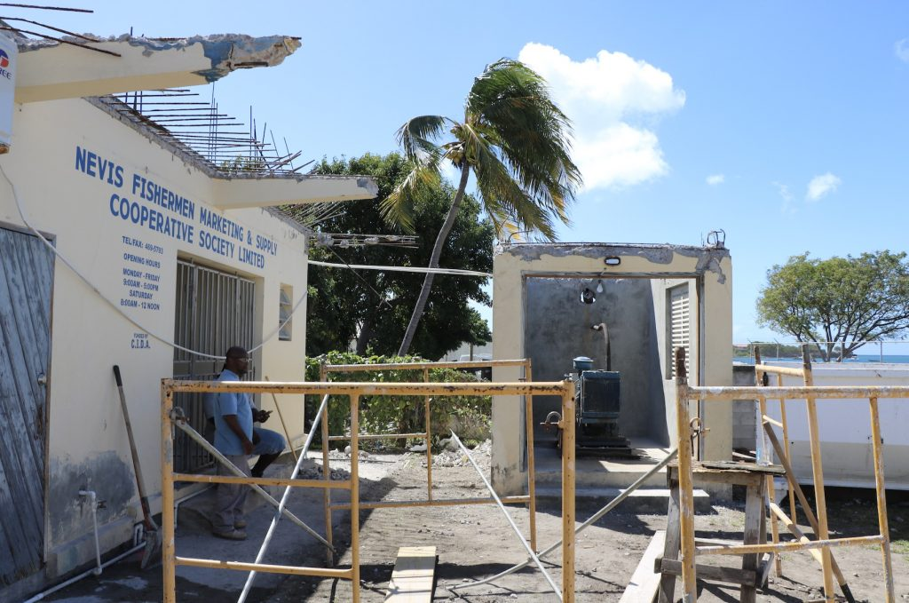 A section of the concrete hangover at the back of the Fisheries Complex in Charlestown along with the concrete roof of the generator room (structure on the right) under repair by the Public Works Department on February 11, 2021
