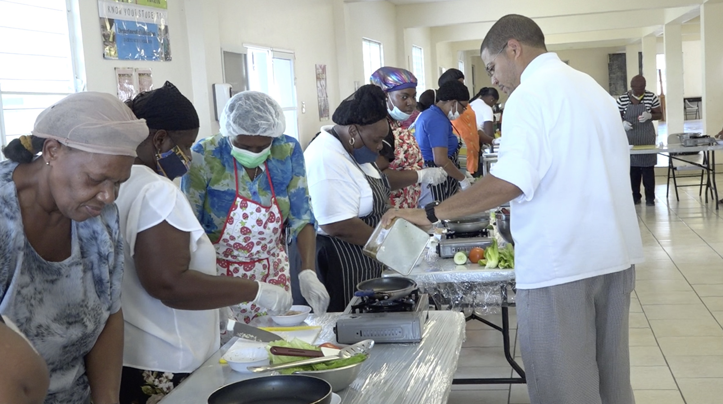 """Chef Michael Henville, Executive Chef and Food and Nutrition Specialist with the Nevis Island Administration's School Meals Programme, training cooking staff in meal preparation for a """"Tour Around the World"""" initiative for primary school students at a session at the Charlestown Primary School's cafeteria on March 10, 2021"""
