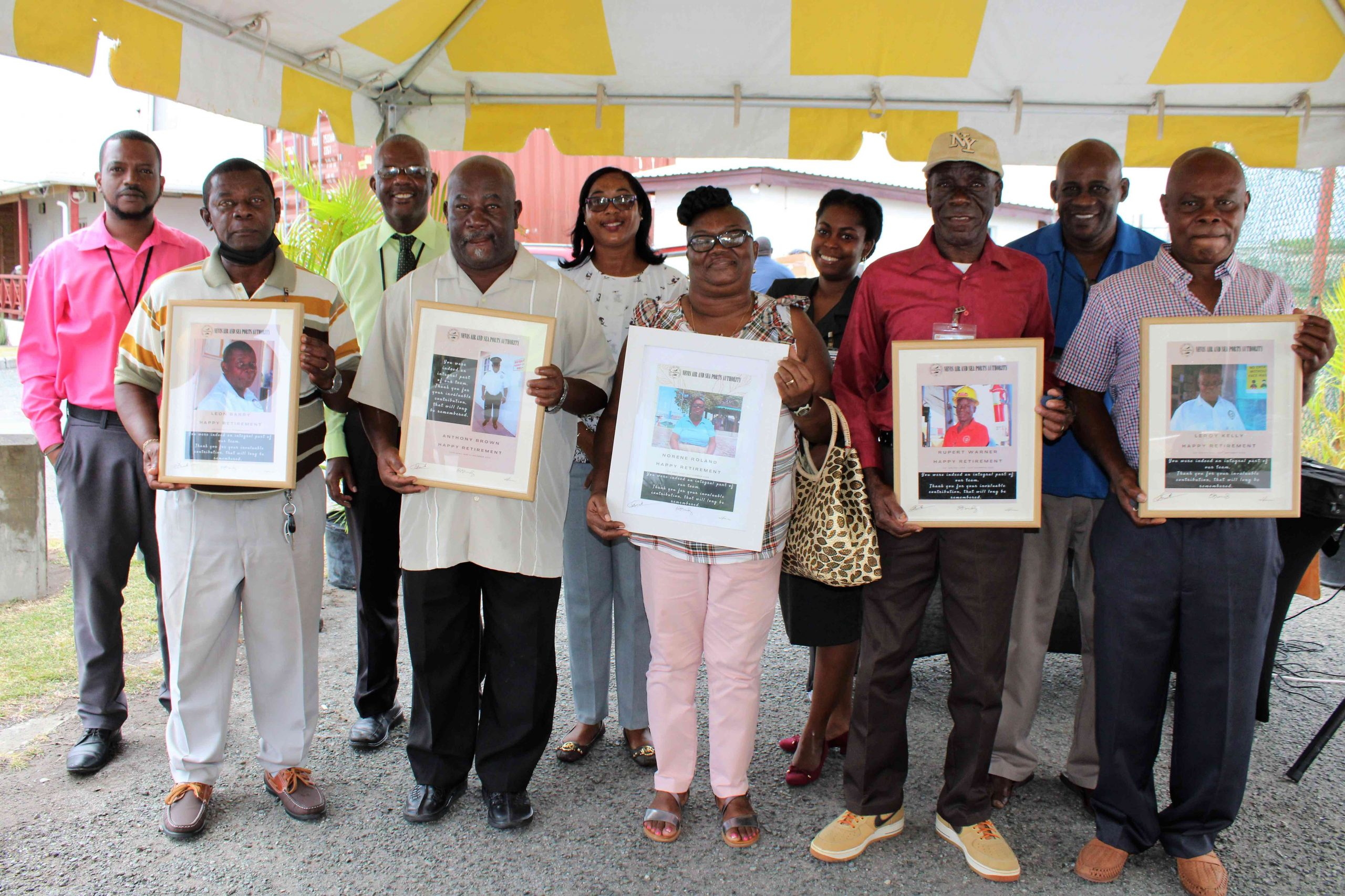 Front row (l-r) Retirees from the Nevis Air & Sea Ports Authority at a ceremony to honour them at Long Point on March 31, 2021 - Mr. Leon Barry; Mr. Anthony Brown; Mrs. Noren Roland; Mr. Rupert Warner; and Mr. Leroy Kelly with officials from the authority - back row (l-r) Mr. Kenyata Warner, Operations Manager at the Charlestown Sea Port; Mr. Oral Brandy, General Manager of the Nevis Air & Sea Ports Authority; Ms. Loretta France, Human Resource Supervisor; Ms. Joanne Flemming, Director of the Nevis Air & Sea Ports Authority Board; and Mr. Joseph Liburd, Chairman of the Board