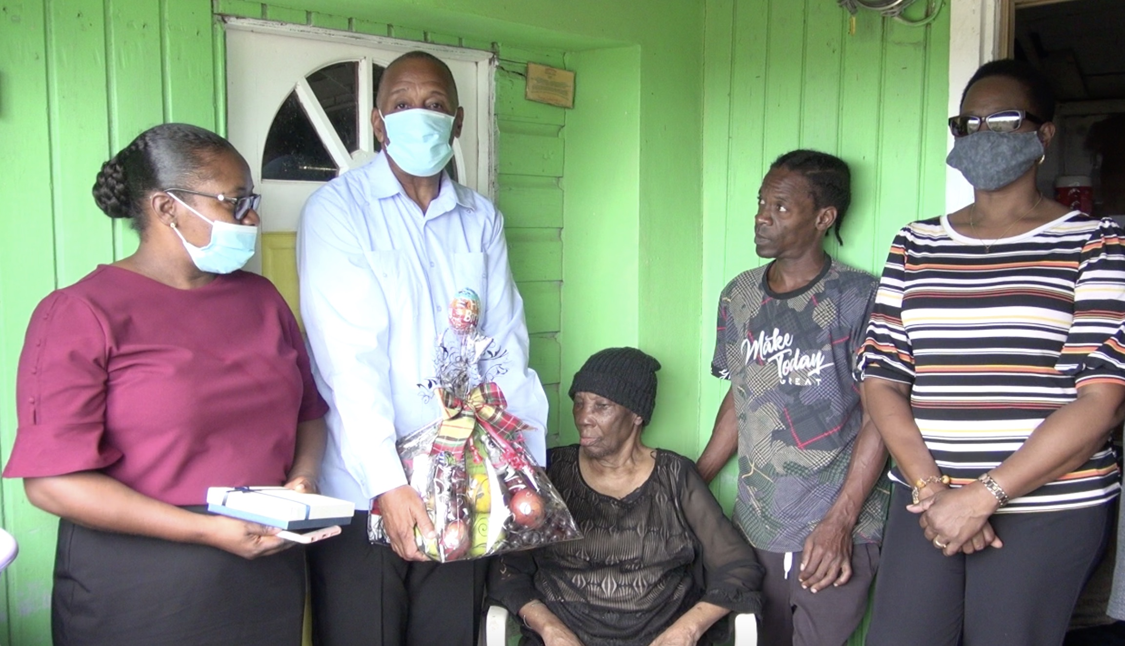 """One hundred and one-year-old Eliza """"Liza"""" Jeffers (sitting) with her nephew Randy at her side while Hon. Eric Evelyn, Minister responsible for seniors on Nevis, presents her with a fruit basket, a token of appreciation on behalf of the ministry and the Department of Social Services' Senior Citizens Division in celebration of National Centenarians Day on May 31, 2021"""