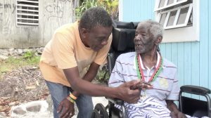 """Mr. Nathan """"Neville"""" Sutton, 100, of Rawlins in Gingerland wearing his medal of honour presented to him by Hon. Eric Evelyn Minister of Social Development on Nevis on behalf of His Excellency Sir Tapley Seaton, Governor General of St. Kitts and Nevis shares a light moment with a close friend moment after he received it in celebration of Centenarians Day on May 31, 2021"""