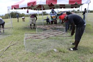Participants constructing fish pots at the Department of Gender Affairs Fish Trap Making Workshop for boys and young men at the Jessups Playing Field on May 08, 2021