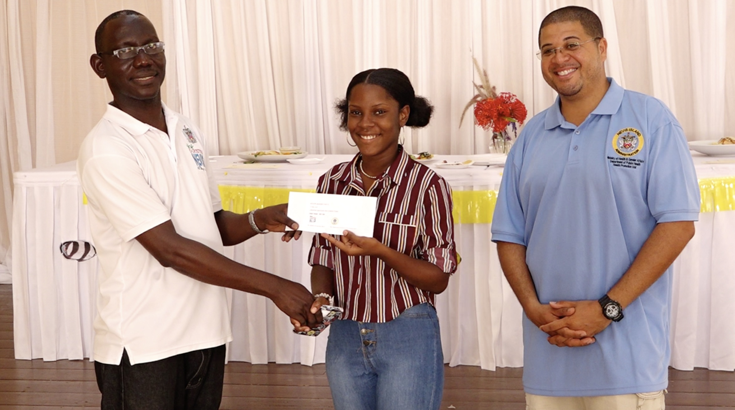 Mr. John Hanley, Permanent Secretary in the Ministry of Tourism, presents Ms. Jermella Browne, winner of the ministry's first Creative Seafood Dish Competition with her prize on May 03, 2021 while Executive Chef Michael Henville, a judge looks on