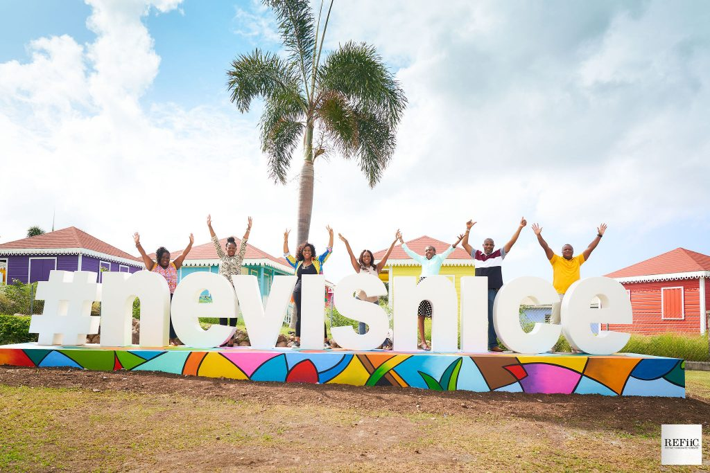 Nevis Tourism Authority staff taking photos with Ms. Jadine Yarde, the authority's CEO (fourth from left) at the new #nevisnice fixture on the Island Main Road outside the Artisan Village at Pinney's (photo provided)